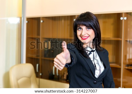Pretty smiling woman in office shows thumb up #314227007