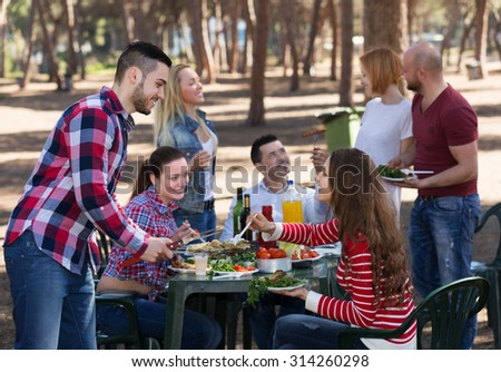 Positive young friends relaxing at grill party in sunny day #314260298