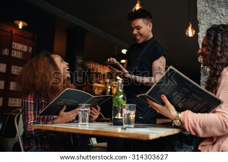 Cheerful two young women sitting at cafe holding menu card giving order to waiter. Young woman placing order to a waiter at restaurant while sitting with her friend. #314303627