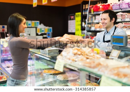 Shopkeeper working in his grocery store #314385857