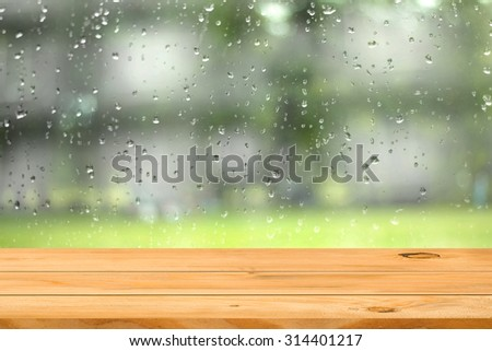 Empty wooden table over water drop on window garden background. Ready for product display montage.
