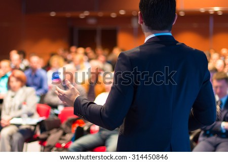 Speaker at Business Conference with Public Presentations. Audience at the conference hall. Entrepreneurship club. Rear view. Horisontal composition. Background blur. #314450846