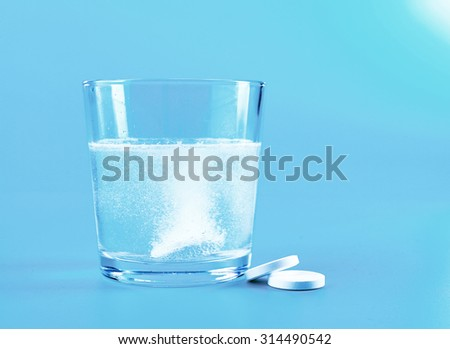Glass of water and pills on blue background #314490542