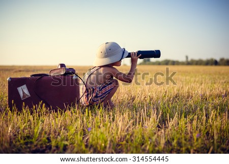 Picture of boy wearing pith helmet and plaid romper looking in spyglass in wheat field. Little explorer with camerabag and old suitcase on sunny countryside background. Royalty-Free Stock Photo #314554445