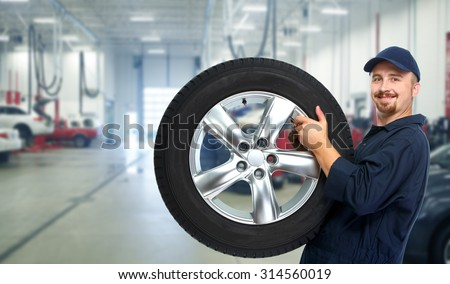 Smiling repairman with tire a in car repair service. #314560019