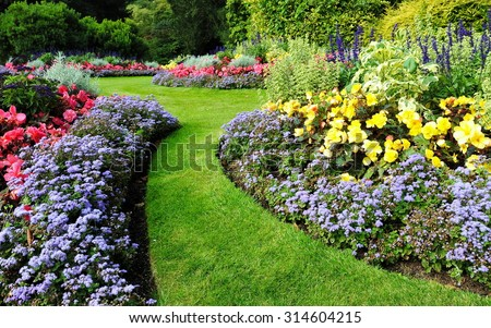 Scenic View of Colourful Flowerbeds and a Winding Grass Lawn Pathway in an Attractive English Formal Garden #314604215