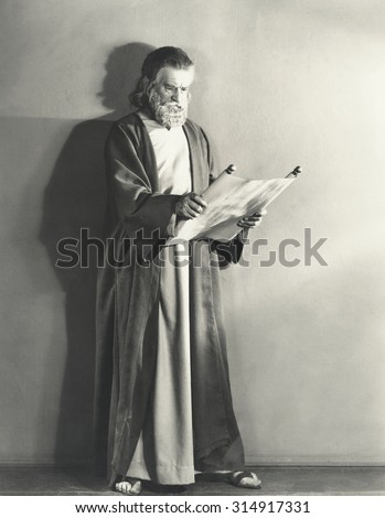Man in robe reading scroll #314917331
