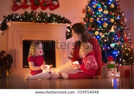 Family on Christmas eve at fireplace. Mother and little kids opening Xmas presents. Children with gift boxes. Living room with traditional fire place and decorated tree. Cozy winter evening at home. #314954048