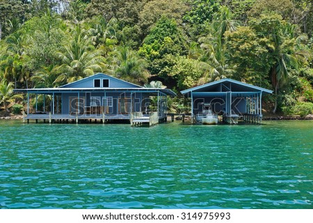 Tropical home and boat house over the sea with lush vegetation on the shore, Panama, Central America #314975993