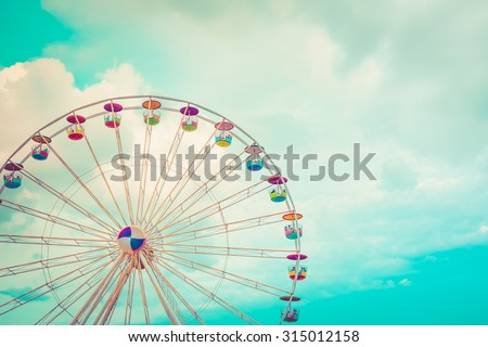 Ferris wheel on cloudy sky background vintage color Royalty-Free Stock Photo #315012158