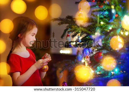Adorable little girl decorating a Christmas tree with colorful glass baubles at home #315047720