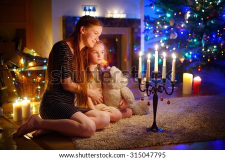 Young mother and her little daughter sitting by a fireplace in a cozy dark living room on Christmas eve #315047795