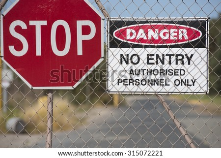 Stop and Danger sign at secured gate of property, no entry, trespassing, blurred background, copy space.