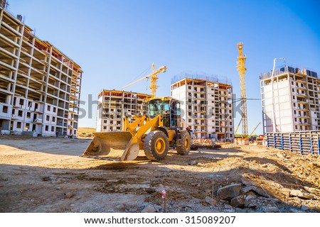 building panorama with the excavator in the foreground Royalty-Free Stock Photo #315089207