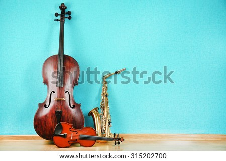 Musical instruments on turquoise wallpaper background Royalty-Free Stock Photo #315202700