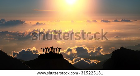 On the top of the world together. A group of people stands on a hill over the beautiful cloudscape. Royalty-Free Stock Photo #315225131