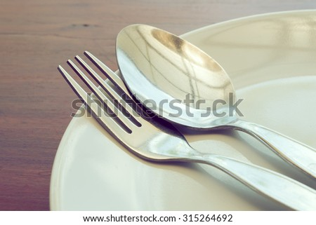 dishware set on wood table with plate, spoon and fork, image used filter vintage #315264692