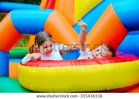 excited kids having fun on inflatable attraction playground #315436136
