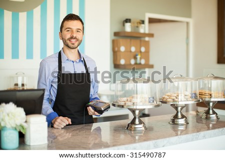 Attractive young Latin man holding a bank terminal next to a cash register in a bakery