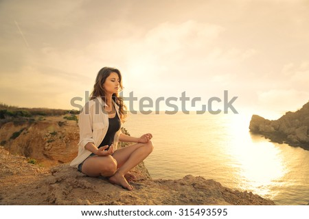 Young woman meditating at the sea Royalty-Free Stock Photo #315493595