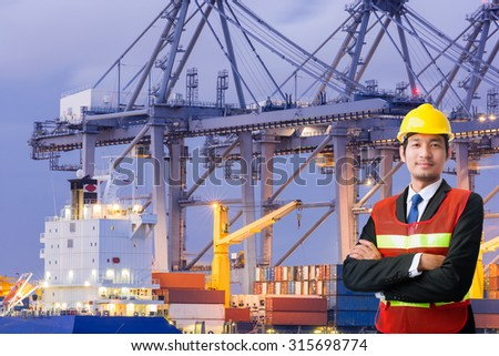 Young engineering man and safety helmet, shirts standing arms crossed against cargo port #315698774