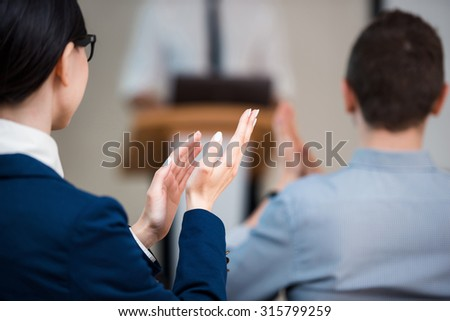 Close up photo of woman hands clapping while businessman making presentation with whiteboard on seminar or meeting to business people #315799259