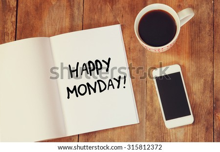 notebook with the phrase happy monday written on it, coffee cup and smart phone. filtered image.