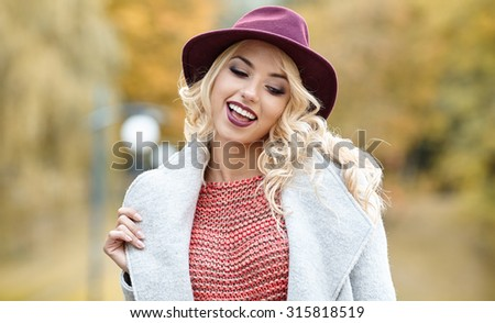 Beautiful elegant woman standing in  autumn park #315818519