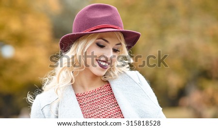 Beautiful elegant woman standing in  autumn park #315818528