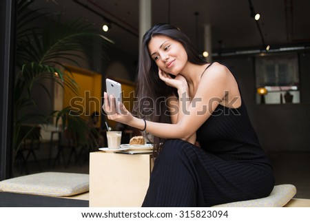 Young latin woman making self portrait on her smart phone digital camera while sitting in sidewalk cafe during lunch break, pretty female posing while photographing herself for social network picture #315823094