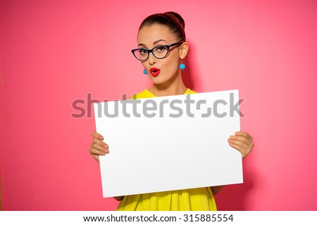 Your text here. Pretty young excited woman holding empty blank board. Colorful studio portrait with pink background. #315885554