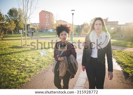 two multiethnic beautiful young woman black and caucasian having fun strolling in a city park, one overlooking right, the other looking in camera - freshness, friendship concept #315928772