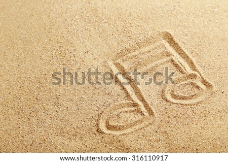 Music note drawn on a beach sand