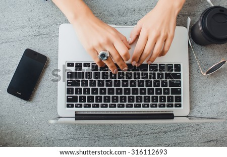 outdoor image of student, teen girls hand working on laptop at street cafe.Overhead of essentials for modern young person. on grey background.Pastel tender colors.Laptop,black phone,coffee break