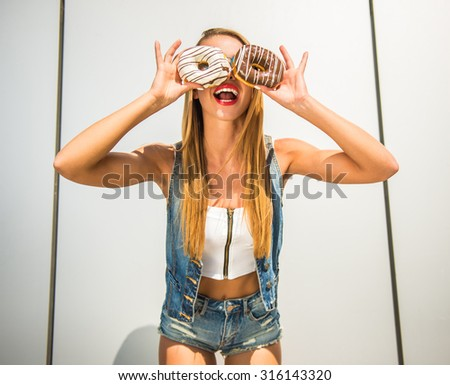 Playful young woman holding donuts against her eyes and smiling while standing against the wall.