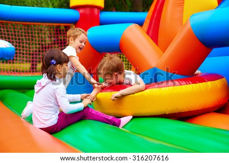 excited kids having fun on inflatable attraction playground #316207616