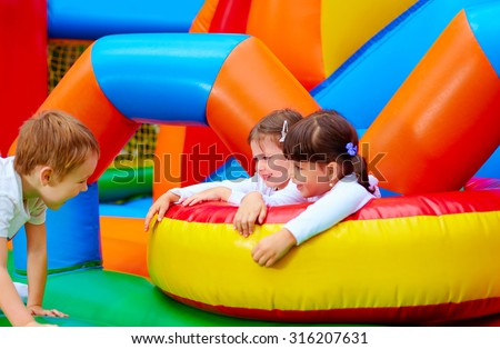 excited kids having fun on inflatable attraction playground #316207631