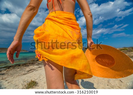 Woman seen from behind with orange sarong and wide brimmed hat on tropical beach. Elafonisos, the Greek version of the Maldives, the island's most exotic Mediterranean, Peloponnese, Greece. #316210019