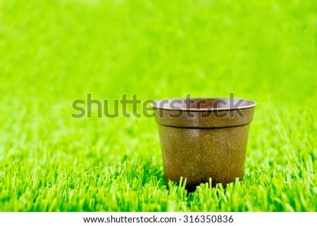 Empty brown flower pot on green grass. #316350836