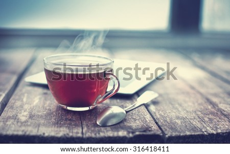Hot tea cup on a frosty winter day window background #316418411