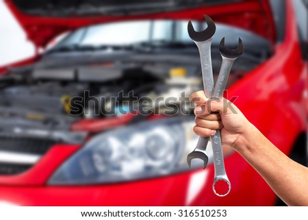 Hand of car mechanic with wrench. Auto repair garage. #316510253