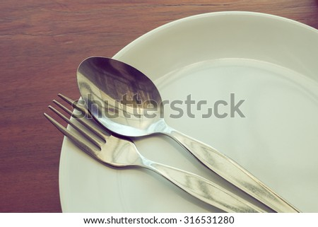 dishware set on wood table with plate, spoon and fork, image used filter vintage #316531280