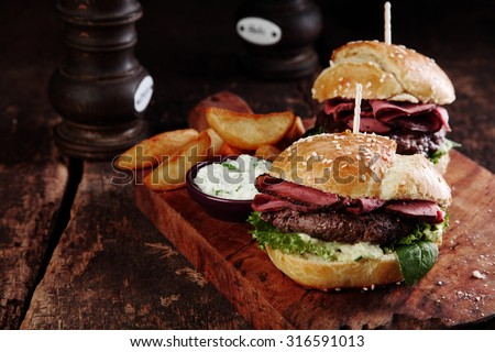 Gourmet Tasty Steak Burgers with Ham Slices on a Wooden Tray with Potato Wedges and Dipping Sauce. #316591013
