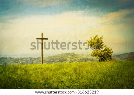 A cross on a green mountain meadow with clouded sky behind.