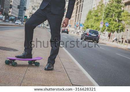 Detail of a young model dressed in dark suit posing with his skateboard #316628321