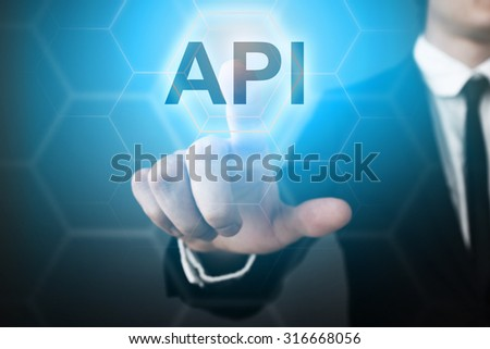 "Businessman pressing touch screen interface and select ""API""."