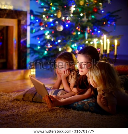 Young mother and her daughters using a tablet pc by a fireplace on warm Christmas evening #316701779