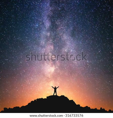 Man and the Universe. A person is standing on the top of the hill next to the Milky Way galaxy with his hands raised to the air.  Royalty-Free Stock Photo #316733576