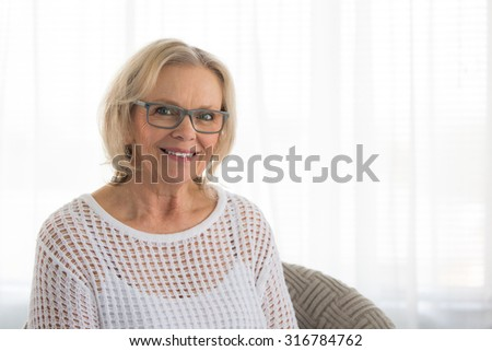 Middle aged blonde woman with glasses smiling while sitting in a chair at home #316784762