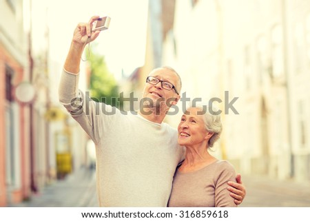 age, tourism, travel, technology and people concept - senior couple with camera taking selfie on street #316859618